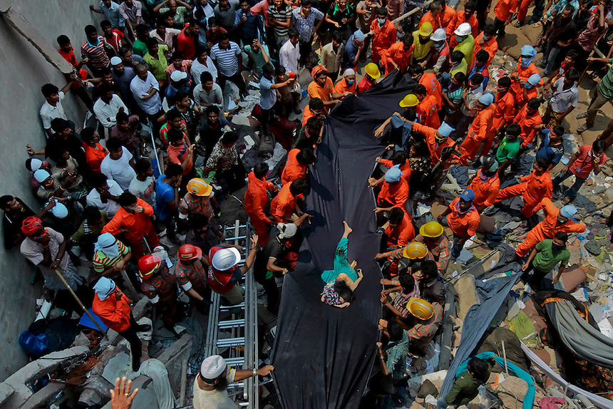 Bangladeshi people watch as rescuers use a piece of fabric to lower the body of a woman after she was discovered inside a building that collapsed Wednesday in Savar, near Dhaka, Bangladesh,Thursday, April 25, 2013.