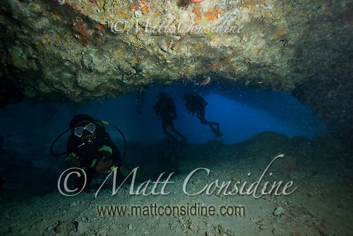 Leaving the aptly named Temple of Doom, with divers in Blue Holes.  Even a few feet from the entrance and exit, there is no light or means of orientation. Even with plenty of artificial light and air, it is easy to see why divers have died here, Palau Micronesia. (Photo by Matt Considine - Images of Asia Collection) (Matt Considine)