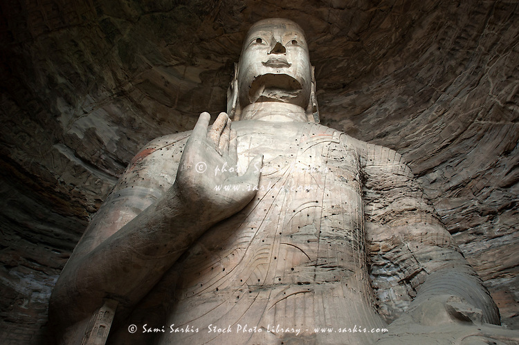 Giant Buddha statue carved inside the ancient Yungang Grottoes, Datong, Shanxi, China.