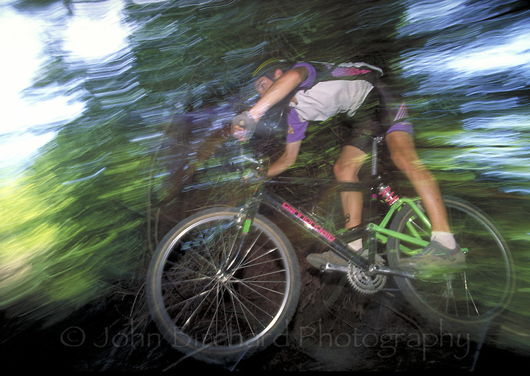 Mountain biking on a trail through redwood forests in Mendocino County, CA.  CD scan from 35mm slide film.  © John Birchard