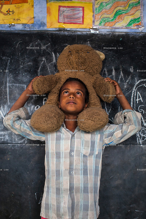 Kallu, 7, poses for a portrait with a soft toy in the Guria Non-Formal Education center in the middle of the Shivdaspur red light district, Varanasi, Uttar Pradesh, India on 20 November 2013. Guria uses the soft toys as a form of therapy for the children of the women in prostitution and also use it as signals of the children's emotional wellbeing.
