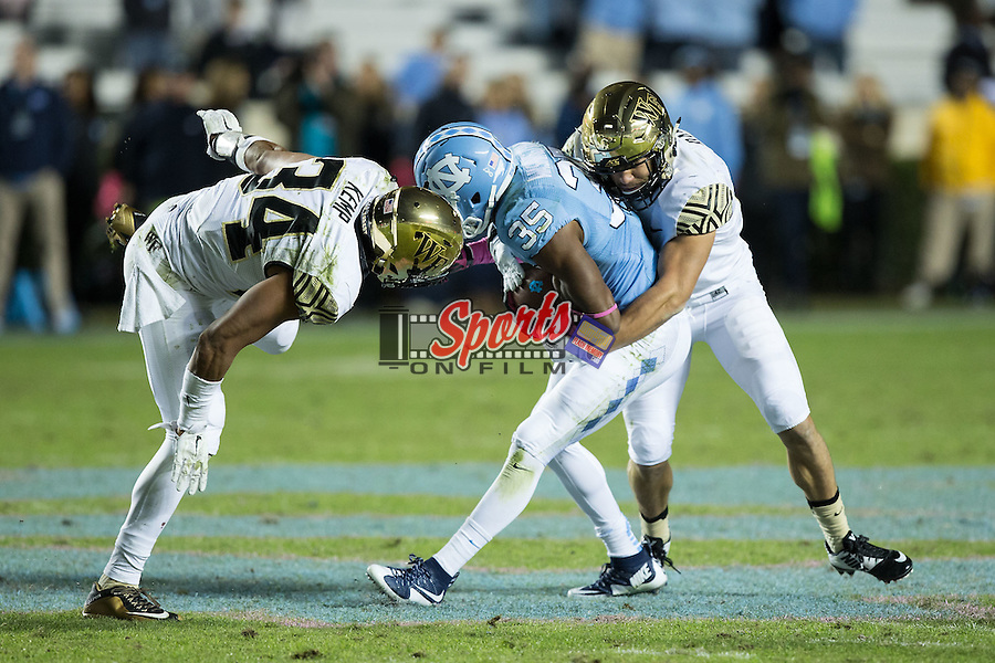 Damien Washington (35) of the North Carolina Tar Heels is hit by Zach Dancel (9) and Demetrius Kemp (34) of the Wake Forest Demon Deacons during second half action against the at Keenan Stadium on October 17, 2015 in Chapel Hill, North Carolina.  The Tar Heels defeated the Demon Deacons 50-14.   (Brian Westerholt/Sports On Film)