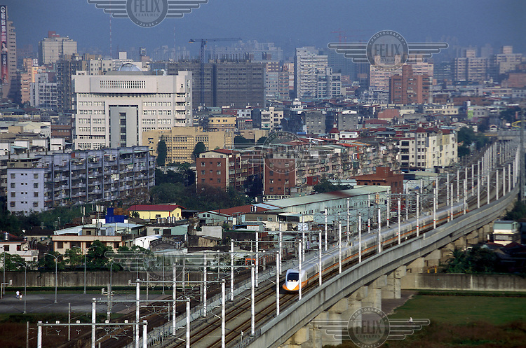 High Speed Rail (HSR) Bullet Train speeding through the Taipei suburbs. The recently completed HSR system speeds the length of the country, a distance of around 400km, in two hours, reaching speeds of 300kmph.