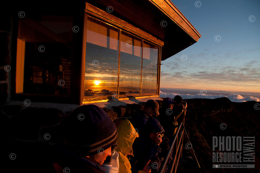 Visitors take in the sunrise, which is reflected in the windows of the visitor center at Haleakala National Park, Maui.