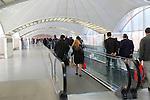 Passengers pulling luggage bags along a bright corridor, Atocha railway station, Madrid, Spain
