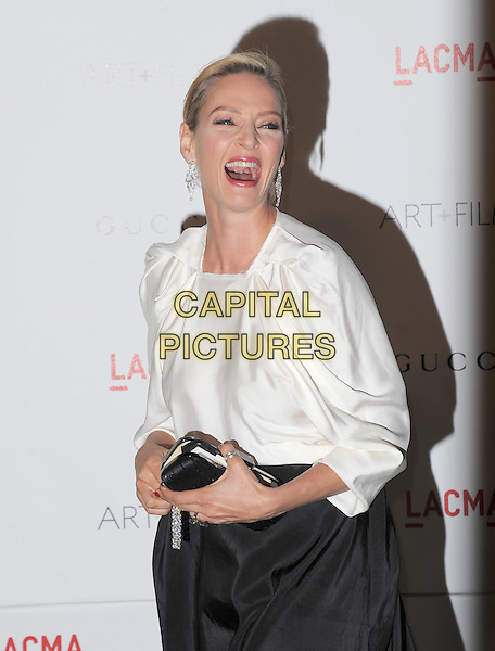 Uma Thurman.The Inaugural Art and Film Gala held at LACMA in Los Angeles, California, USA..November 5th, 2011   .half length black skirt clutch bag white mouth open laughing diamond dangling earrings funny bracelet broken .CAP/RKE/DVS.©DVS/RockinExposures/Capital Pictures.