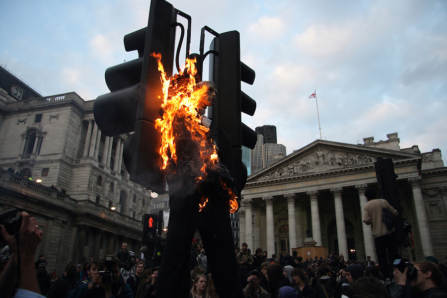 A manikin dressed in bankers clothing is set of fire in front of the Bank of England at the G20 Demonstration.