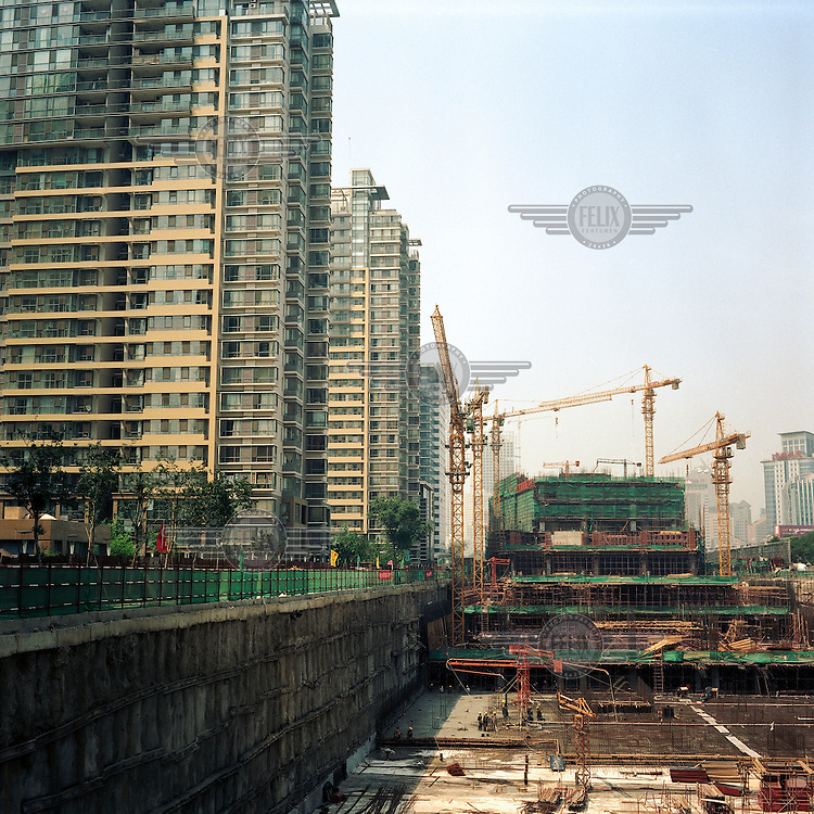 Construction cranes stand on a building site next to a row of high-rise flats.