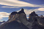 The Cuernos del Paine or the Horns with Cerro Cuerno Principal or Main Horn (2110 m. – 6923 ft.) in front,  Cerro Cuerno Este or East Horn at right, and Cerro Cuerno Norte or North Horn at left and behind.  The yellow granite base with a black sandstone cap gives these formations their very distinctive look.  Torres del Paine National Park in Patagonia, Chile.  A UNESCO World Biosphere Reserve.