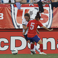 USWNT midfielder Heather O'Reilly (9) battles through Korea Republic midfielder Lee Sejin (5). In an international friendly, the U.S. Women's National Team (USWNT) (white/blue) defeated Korea Republic (South Korea) (red/blue), 4-1, at Gillette Stadium on June 15, 2013.