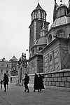 Nuns walk past Wawel Cathedral of Wawel Castle in Krakow, Poland. The current Wawel Cathedral was constructed in the 14th century and is also known at the Cathedral Basilica of St. Stainslaw (a Bishop of Krakow in the 11th century who was martyred by King Boleslaw II the Bold and who lies in the silver coffin under the black marble canopy of the main altar).