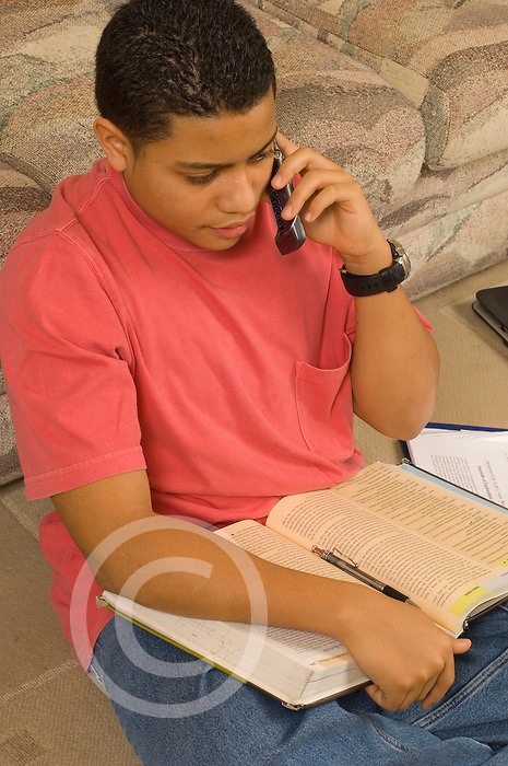 15 year old teenage boy at home sitting in living room using cell telephone Hispanic Puerto Rican