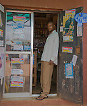 A salesman at a patent proprietary medicine vendor (PPMV) shop in Enugu, Nigeria stands in the door of his shop.  The door and window sport advertisements of various health products.
