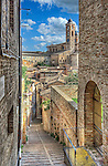 A laneway in the medieval town of Urbino, a walled city in the Marche region of Italy. The town, nestled on a high sloping hillside, retains much of its picturesque medieval aspect.