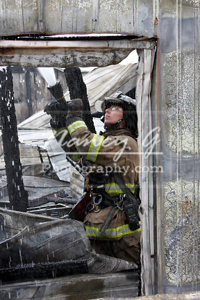 A firefighter extinguishing a fire with a hoseline