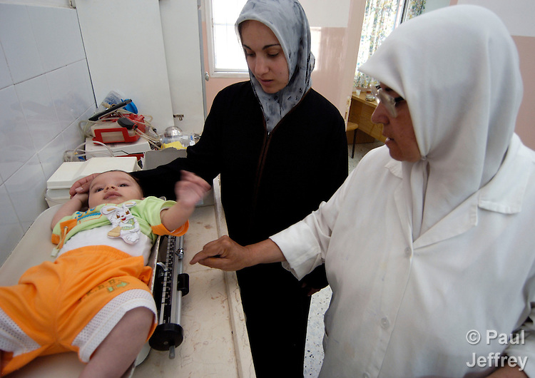 A mother and nurse weigh a baby in the health center of the Ama'ri Refugee Camp in Ramallah.