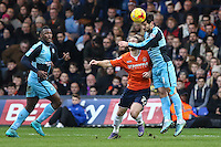 Joe Jacobson of Wycombe Wanderers (right) wins an aerial battle against Craig Mackail-Smith of Luton Town (2nd right) as Aaron Pierre of Wycombe Wanderers (left) looks on during the Sky Bet League 2 match between Luton Town and Wycombe Wanderers at Kenilworth Road, Luton, England on 26 December 2015. Photo by David Horn.