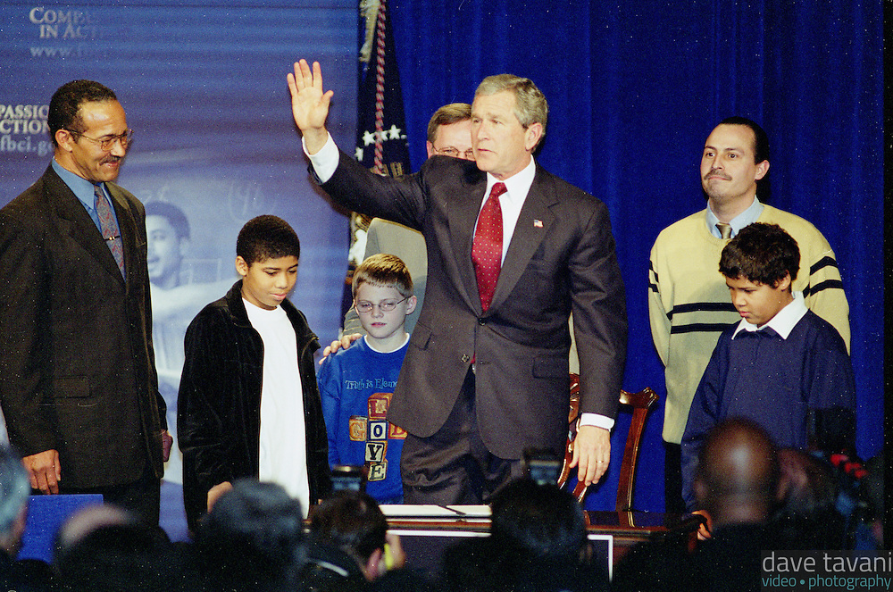 U.S. President George W. Bush waves to the crowd after signing an executive order regarding his Faith Based Initiative Plan in front of community and religious leaders at the Philadelphia Marriott December 12, 2002, in Philadelphia, Pennsylvania.