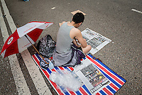 Hong Kong, Government Offices, 2 October 2014<br /> <br /> Students and other supporters of the Occupy Central movement congregating around the government offices area at Tamar. All the roads in the area are blocked from traffic and public transport.<br /> Printed newspapers are still being read by the activists.<br /> <br /> Photo Kees Metselaar