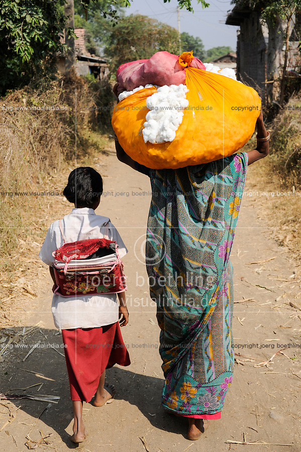 INDIA, Madhya Pradesh , farmer of cooperative produce fairtrade and organic cotton, mother and daughter going home to the village, woman comes with harvested cotton from field, child with school bag from school / INDIEN Madhya Pradesh , Farmer Kooperative baut fairtrade und Biobaumwolle an, Mutter mit Tochter auf Heimweg von Schule und Feld