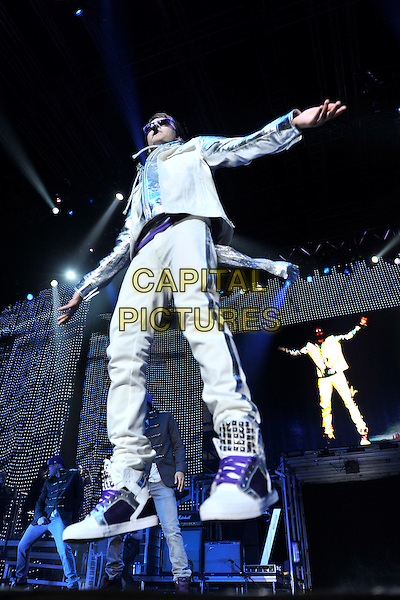 JUSTIN BIEBER.preforms at the National Indoor Arena, Birmingham, England 4th March 2011.live on stage performance gig concert singing full  length sunglasses white jacket hoodie purple trainers trousers hi-tops arms outstretched  dancing jumping   silver sleeves music .CAP/MAR.© Martin Harris/Capital Pictures.