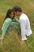 Couple sitting & relaxing in tall grass<br />