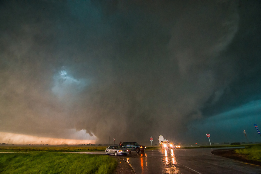 A deadly tornado approaches Interstate 40 southeast of El Reno Oklahoma on May 31st, 2013 as a research radar truck collects key scientific data. This storm resulted in the deaths of 8 people (all in vehicles). Tim and Paul Samaras along with Carl Young, all prominent storm chasers, died when their vehicle was overtaken on a rural road just minutes before this image was taken. This tornado now holds the world record in path width at 2.6 miles.