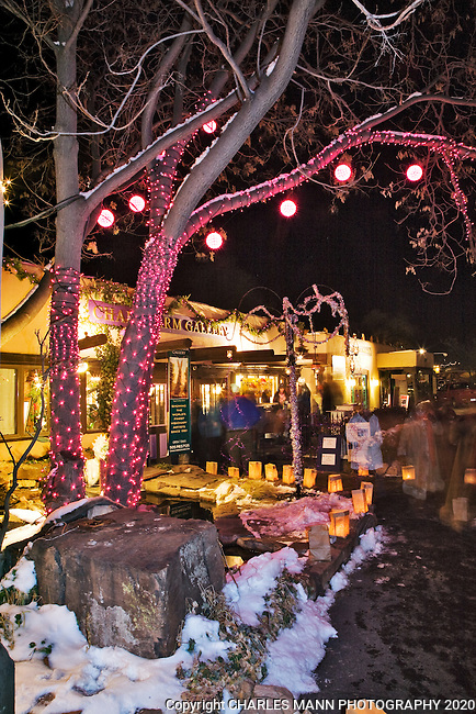 Galleries and stores on Canyon Road in Santa Fe decorate their buildings with lights and paper bag lanterns called faralitos during the annual Christmas Eve celebrations.