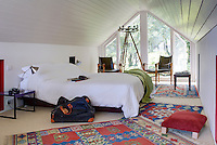 An attic bedroom with a painted panelled ceiling and a floor to ceiling window. The room is furnished with a double bed and two wood and leather armchairs are placed in front of the window. Red and blue pattern rugs add colour to the room.