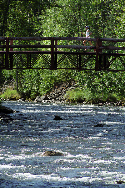 Julie Udchachon crosses the Resurrection River on her way to setting a course record during the 2004 Resurrection Pass Trail 50-Miler ultramarathon foot race. The course follows the trail through the Kenai Mountains and the Chugach National Forest between Cooper Landing and Hope, Alaska.