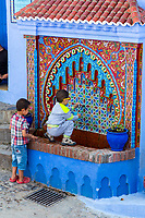 Chefchaouen, Morocco.  Two Young Boys Getting Water at a Public Water Tap.