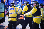 © Joel Goodman - 07973 332324 . 01/01/2016 . Manchester , UK . Police detain a man in handcuffs and take him in to the back of a police van . Revellers in Manchester on a New Year night out at the clubs around the city centre's Printworks venue . Photo credit : Joel Goodman