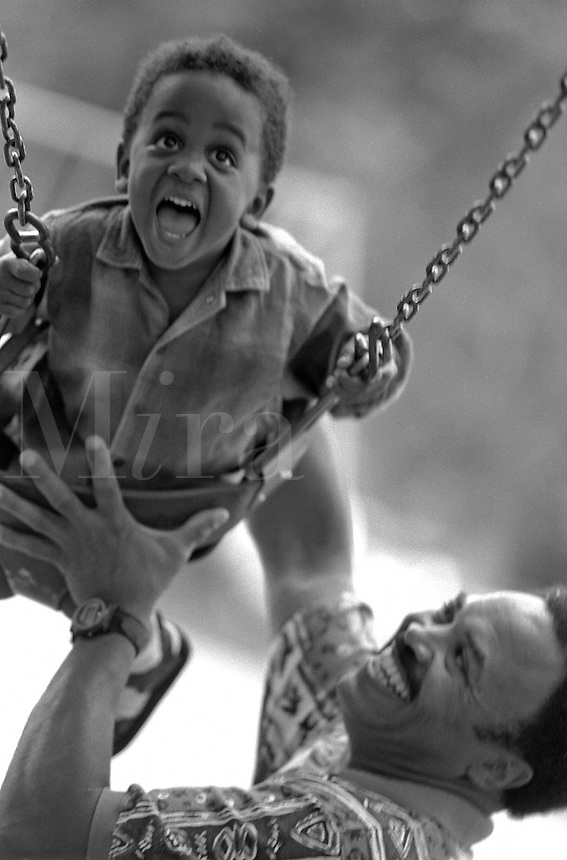 African-American father swinging young son in city park; open-mouthed expression of delight on child's face from experience of momentum; fun, family activities, parents, children, Black child, man, black and white image. Dave Johnson, Gus Hoffman.