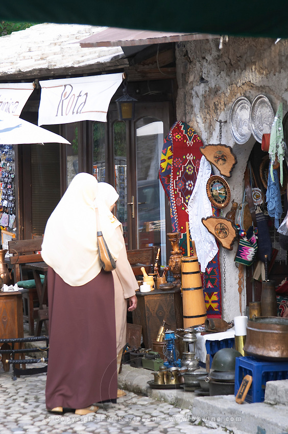 The busy old market bazaar street Onescukova street with lots of tourist craft and art shops and street merchants. Two women in traditional Muslim clothes. Shop selling souvenirs. Historic town of Mostar. Federation Bosne i Hercegovine. Bosnia Herzegovina, Europe.