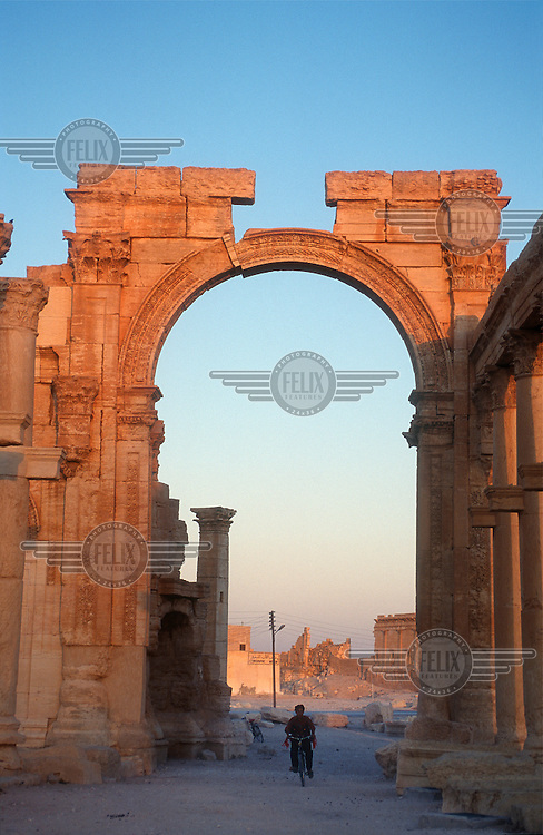 A man cycles through the ancient ruins of Palmyra (or Tadmor in Arabic). The site dates back to the Neolithic period and was first mentioned in the second millennium BC as a caravan stop. It later came under the Seleucid Empire and then under the Roman Empire.<br /> In May 2015 Islamic State (IS) forces fighting the Syrian government of President Assad took control of the modern settlement of Tadmur and the historic site. There are fears that the priceless treasures could fall victim to IS's iconoclastic destruction that has seen museums and ancient sites across Syria and Iraq destroyed.