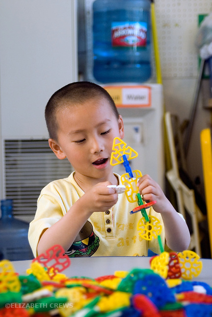 Berkeley CA  Four-year-olds concentrating on building with construction toy in solitary play at preschool