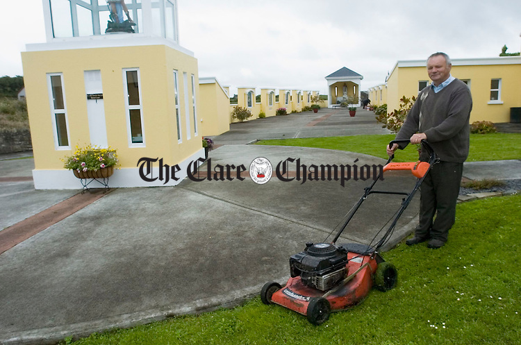 Eddie Donnellan works on the grass at St Michael's Shrine, Kilmihil, in preparation for the Pride of Place adjudication. Photograph by John Kelly.