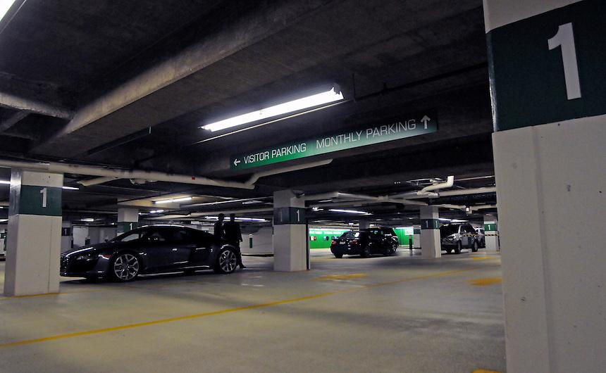 An audi R8 in the basement parking garage of an office tower.