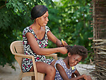 Darlie Joseph braids the hair of her daughter Lovedaline in Picmy, a village on the Haitian island of La Gonave where Service Chrétien d'Haïti is working with survivors of Hurricane Matthew, which struck the region in 2016. A member of the ACT Alliance, SCH is helping families like hers to repair or rebuild their homes while also jump-starting their agricultural production.