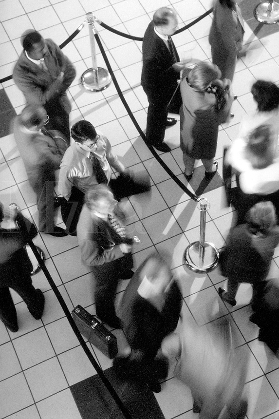 Business people waiting in a slow line. United States.