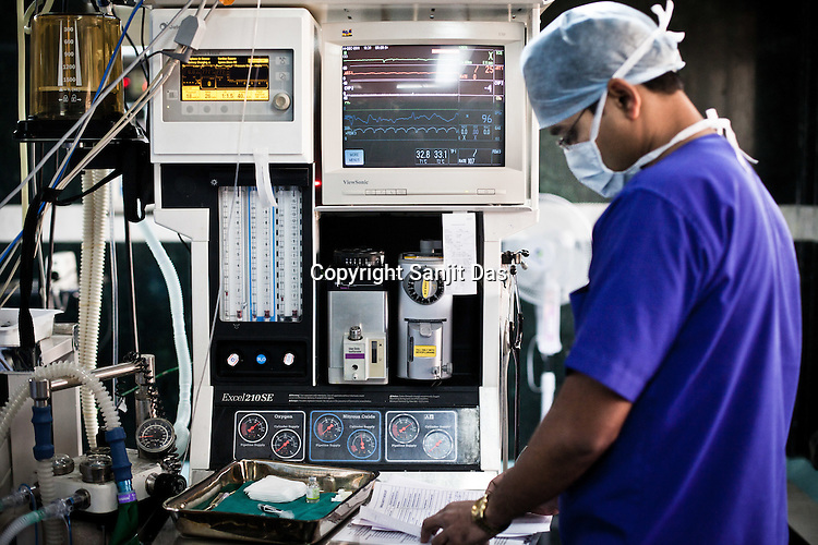 A anesthetist seen next to the machines manning the patient during  an open heart surgery at operation theatre of the Narayana Hrudayalaya in Bangalore, Karnataka, India. Photo: Sanjit Das/Panos