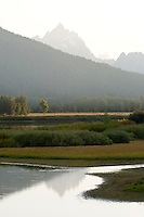 Mt. Teewinot peeks over a ridge and reflects in still waters of Oxbow Bend at sunset