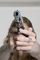 Caucasian blonde woman pointing handgun