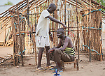 Racen Ali gives Pikem Mahadi a haircut in the Doro Refugee Camp in Maban County, South Sudan. Doro is one of four camps in Maban that together shelter more than 130,000 refugees from the Blue Nile region of Sudan. Jesuit Refugee Service provides educational and psycho-social services to both refugees and the host community. <br /> <br /> Misean Cara supports the work of JRS in the Maban camps.
