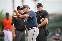 GCL Braves manager Nestor Perez (4) argues a call with umpires Chris Argueza (left) and Chad Patterson (right) during a Gulf Coast League game against the GCL Orioles on August 5, 2019 at Ed Smith Stadium in Sarasota, Florida.  GCL Orioles defeated the GCL Braves 4-3 in the first game of a doubleheader.  (Mike Janes/Four Seam Images)