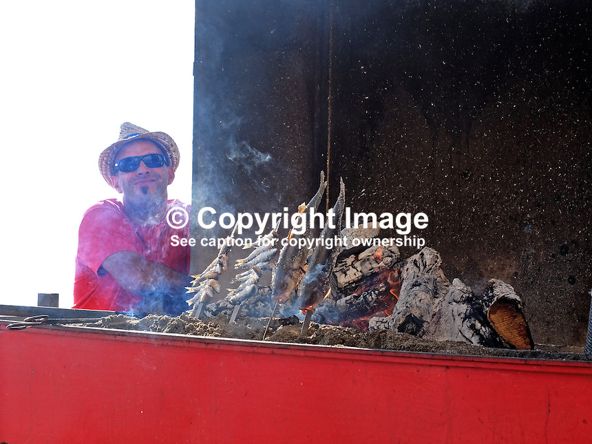 Chef at a chiringuito, open-air beach restaurant, cooking grilled sardines, seabass for clientsin Marbella, Malaga, Spain, Espana, 201412150224<br />