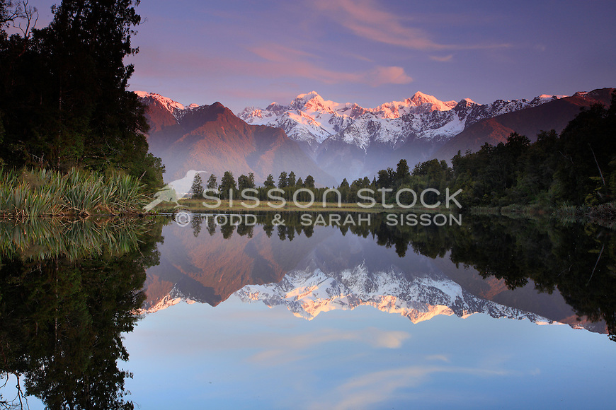 Perfect mirror reflections of the Southern Alps at sunset.  Lake Matheson (near Fox Glacier), Westland Tai Poutini National Park. New Zealand.