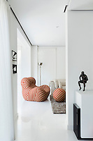 The dining room is separated from the sitting area by a partition wall. A red striped Zingy chair by Gaetano Pesce brings fun and colour to the predominately white palette of the room.