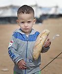 Two-year old Majed, a refugee from Syria, carries bread through a camp for refugees who have arrived on the Greek island of Chios after crossing the Aegean Sea in small boats from Turkey. They are registered and provided with food and shelter in a reception center built with support from International Orthodox Christian Charities, a member of the ACT Alliance. Hundreds of thousands of refugees and migrants have passed through Greece in 2015 on their way to western Europe.