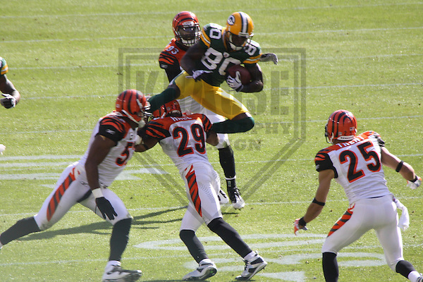 GREEN BAY - SEPTEMBER 2009:  Donald Driver (80) of the Green Bay Packers leaps over Bengals defenders during a game on September 20, 2009 at Lambeau Field in Green Bay, Wisconsin. (Photo by Brad Krause)